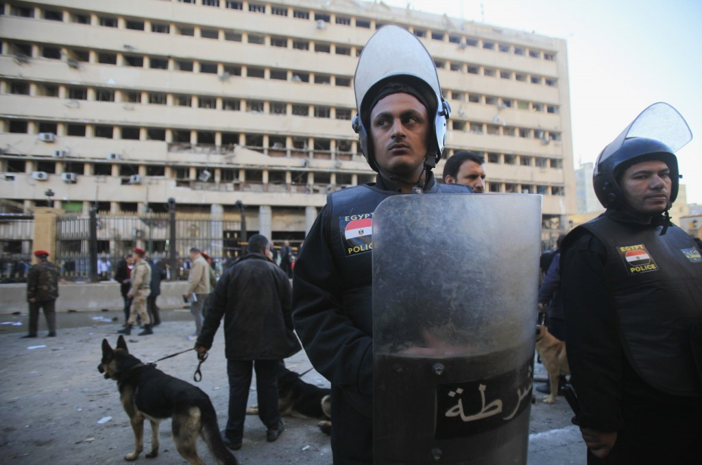 Police officers stand guard in front of damaged Cairo Security Directorate after bomb attack in Cairo